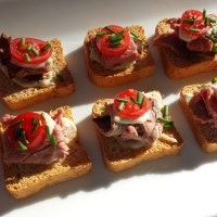 Mini-toasts with Roast Beef, Horseradish Sauce, Grape Tomato Slices and Chopped Chives
