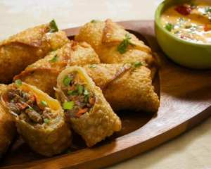 Eggrolls on a wood plate with cheese dip