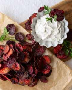 Sliced baked red beet chips on a brown paper bag with sour cream dip