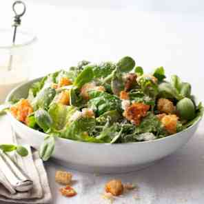 A salad in a white bowl on a white tablecloth