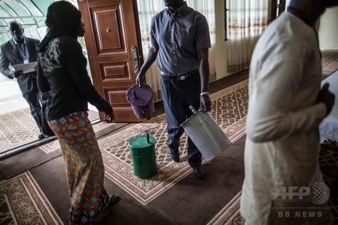 ガンビア・セレクンダにあるホテルの会見場で、大統領候補者別に色分けされた投票用のドラム缶を運ぶ男性(2016年11月28日撮影)。(c)AFP/Marco LONGARI