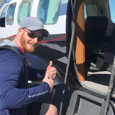 Man wearing sunglasses giving 2 thumbs up while boarding small plane.