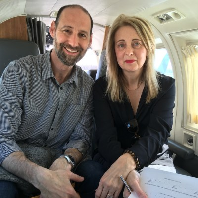 Dr Ian Shulman and a woman sitting on an airplane.