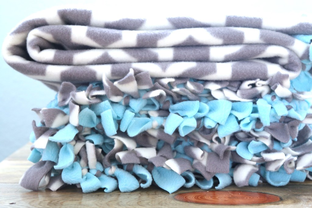 Are you ready for the simplest tutorial around? I will show you how to make a tied fleece blanket for everyone on your shopping list. Get ready to snuggle! TIED FLEECE BLANKET