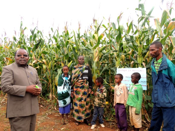 Cade Mshamu, the Babati district's administrative secretary speaks to a farmer, taking part in the project's demonstrations, and his family