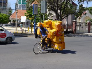 manonbicycletransportingcannisters-scaled