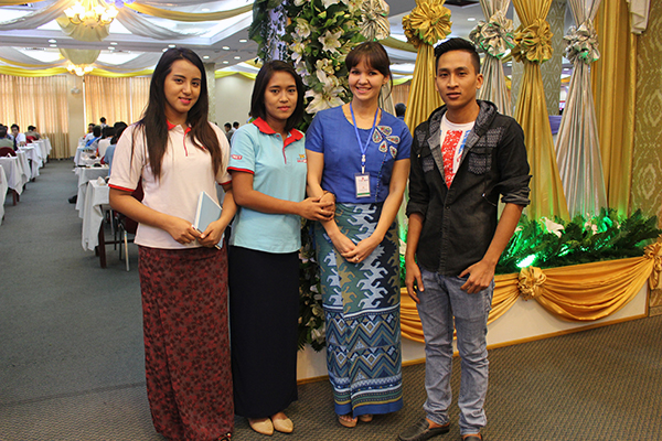 Alexandra wearing the traditional Burmese longyi in Yangon surrounded by staff from the local TV station