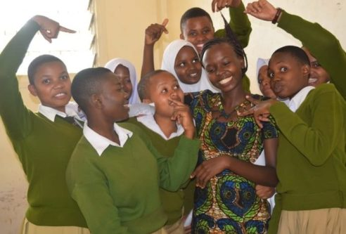 Kisa Scholars taking photo with their Mentor in the classroom | donate | AfricAid | Denver, CO.