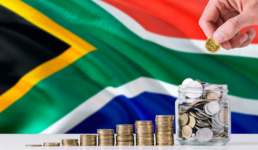 in the background is a south african's flag. In the foreground is a hand with some coins.