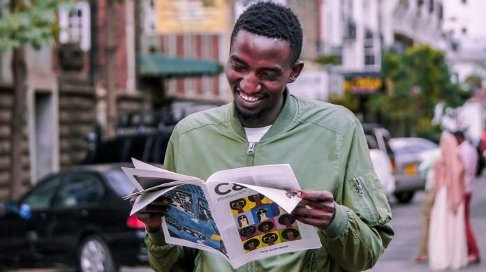 Kenyan man reading a magazine