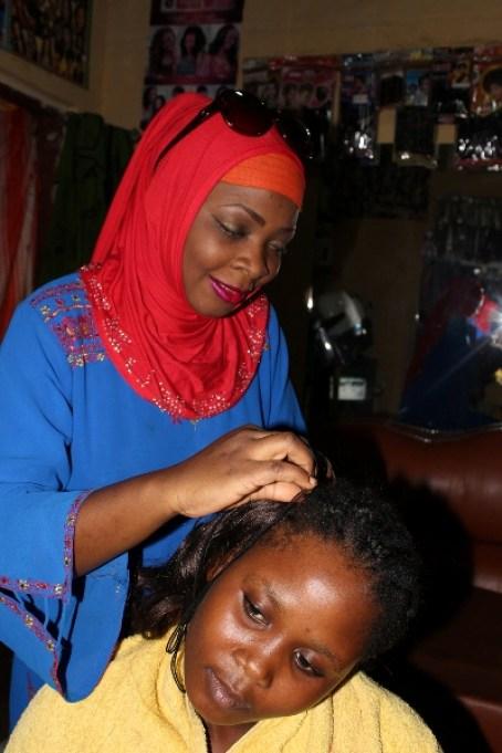 Aisha entrain de coiffer une cliente, Sunrise, 2018.