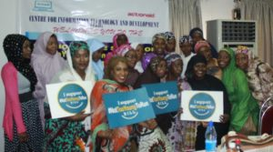 Female participants at the debate holding placards of the #NotTooYoungToRun campaign posed for a group photo shortly after the event