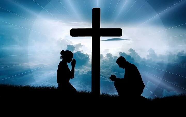 A couple praying for health under the cross of Jesus