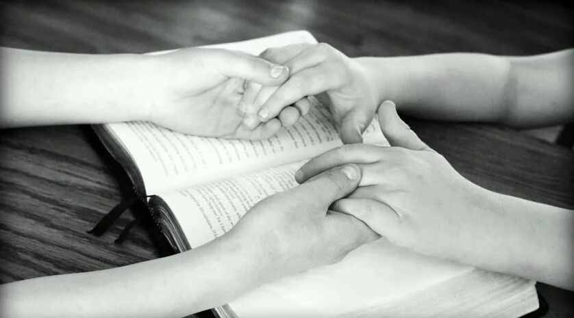Two people holding hands in prayers