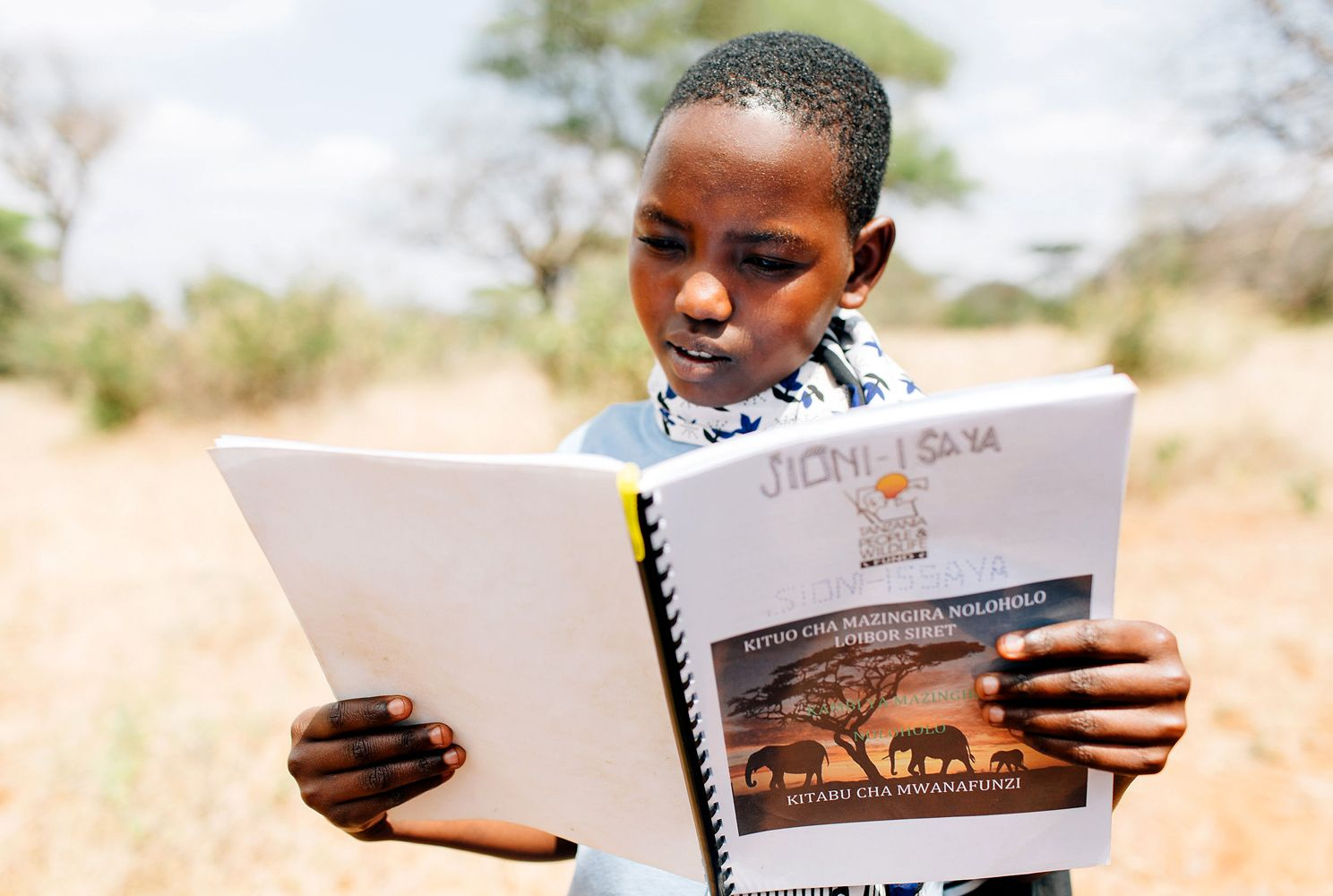 A Tanzanian girl reads a workbook during an APW environmental summer camp.
