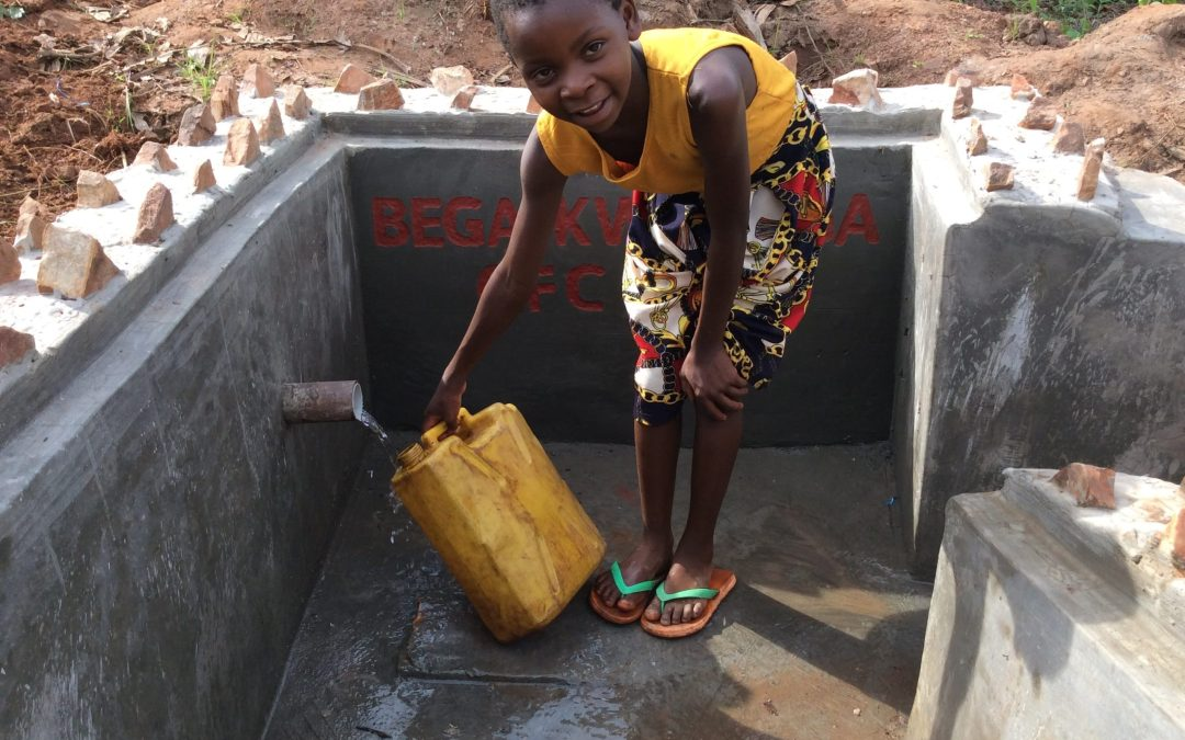 Child fetching water from the well after construction-min
