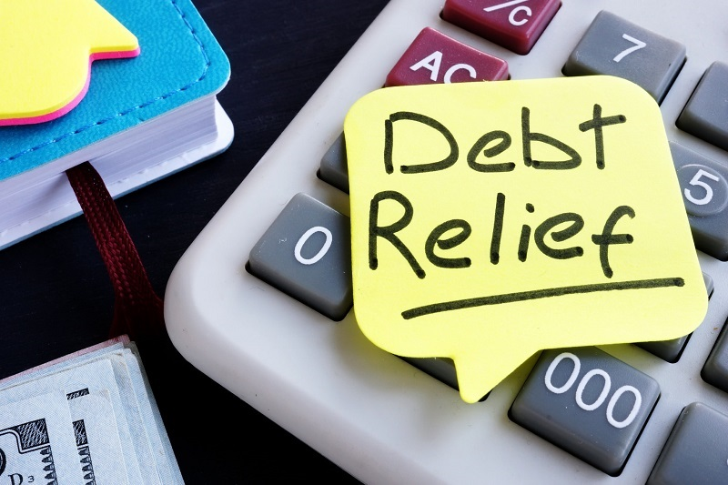 Post note reads debt relief placed on calculaor