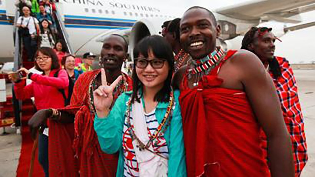 Chinese girl and African people smiling in front of airplane