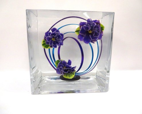 Underwater design using a glass cube with three double blue violet flowers and loops of purple and blue wire