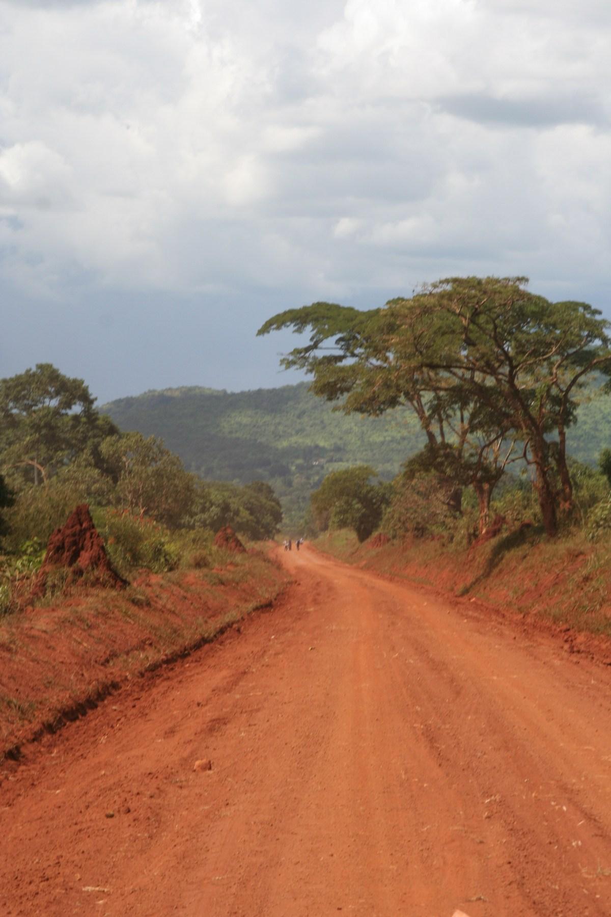 Western Uganda red dirt road and travellers