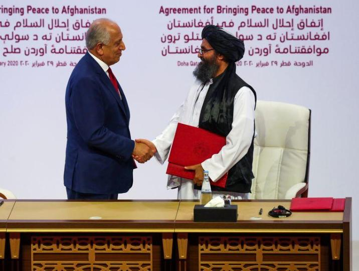 A representative from the United States and a Taliban leader at the drawing of the peace agreement on Saturday.