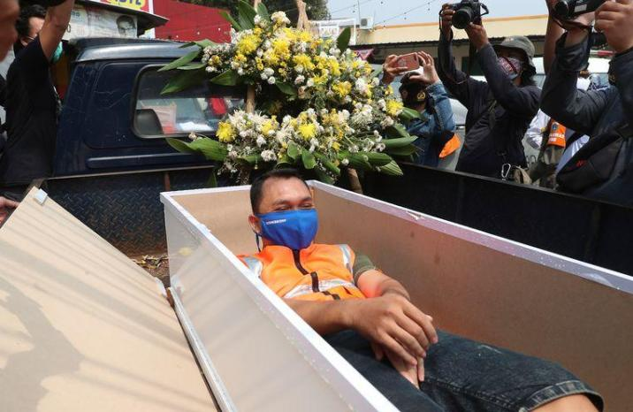 Indonesian man lying in the open coffin