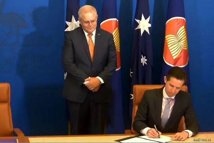 Australia was not missing either. Prime Minister Scott Morrison watches as Secretary of Commerce Simon Birmingham signs.