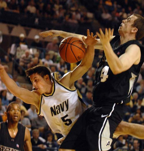 Navy's Chris Harris and Army's Eric Zastoupil get tangled up under the hoop during Saturday's Army-Navy game in Annapolis.  Navy beat Army 62-56. (Tom Brown/ Staff)