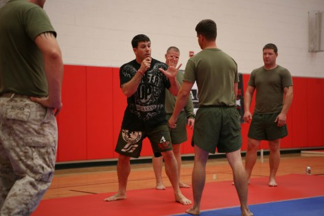 Staff Sgt. Jonathan Walsh, a Mixed Martial Arts fighter from Marine Corps Base Camp Pendleton, explains the importance of distance to surrounding Marines during a MMA visit Oct. 27. During the visit MMA fighters taught Marines the basics of MMA techniques. 	Cpl. Deanne Hurla/USMC