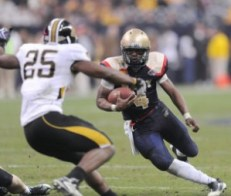 Navy quarterback Ricky Dobbs eludes a tackle against Missouri last year. (Navy photo)