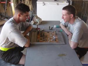 Soldiers with 1-7 Field Artillery play a quiet game of chess on Independence Day at FOB Summerall, Bayji, Iraq, 2004. (Photo by Gina Cavallaro)