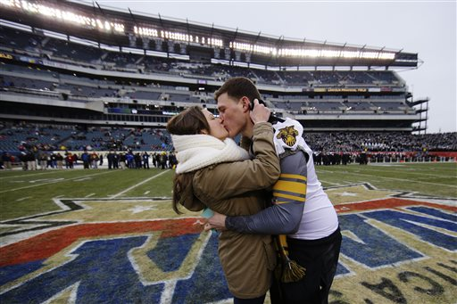 Army senior offensive lineman Colin Joy, right, and Nicole Veroline kiss after Joy proposed to her on the field before the Army-Navy game, Saturday in Philadelphia. She said yes. The couple is from Long Island, N.Y. (AP Photo/Matt Slocum)
