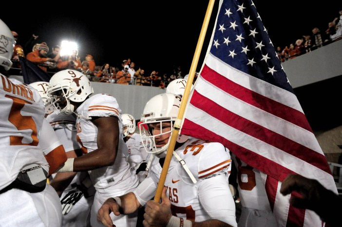 Nate Boyer prepares to carry the flag onto the gridiron before a Texas-West Virginia game in 2013. The former Green Beret hopes to crack an NFL roster as a long snapper this season. (USA Today Sports photo by Evan Habeeb)