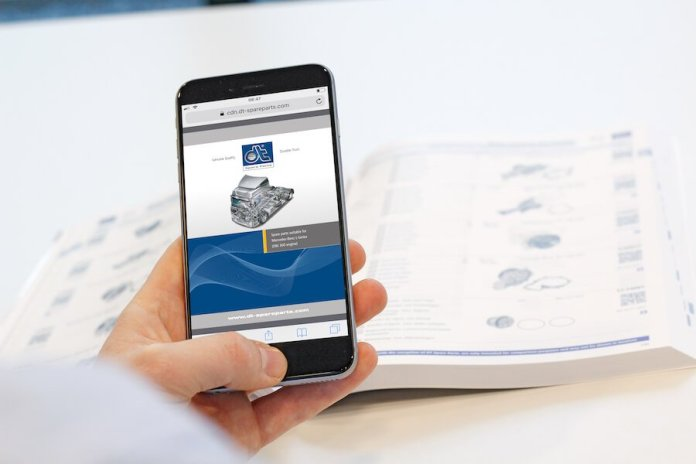 This is an image of a person holding a smartphone in their left hand while viewing the DT Spare Parts online catalog. In the background, there is a paper auto parts catalog.