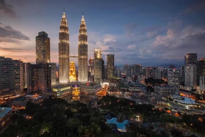 This photo shows Kuala Lumpur, Malaysia, where Automechanika Kuala Lumpur 2019 will take place. It is a general view of the city. At left of center, is the twin Petronas Towers. It is a photo of gleaming office towers at night in this modern city.