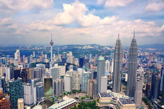 This is a daytime photo of Kuala Lumpur, Malaysia. Shown is a modern cityscape with tall office towers. In the background, a mountain range can be scene with more buildings.