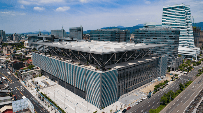 This image shows an aerial view of the new Nangang Exhibition Center 2 in Taipei. The photo is taken from a corner of the center and shows several mid-rise buildings in the background.