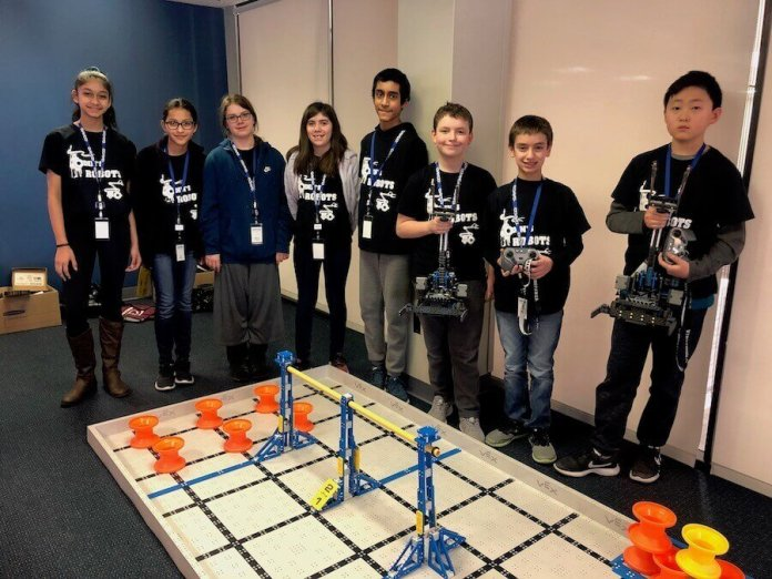 Members of the Van Hoosen Middle School Robotics Team stand for a photo, some holding robots in their hands.