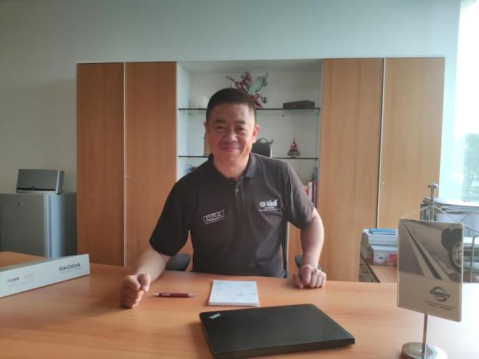 Zhongchuan Cao, General Manager of Tantivy Automotive, stands and smiles at a counter.