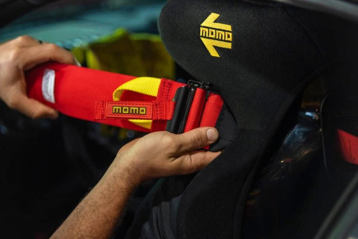 This image shows someone's hands adjusting a red Momo harness.