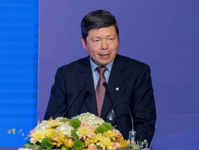 TAITRA President & CEO Walter Yeh stands at a podium in front of a flower display during the show's opening ceremonies.