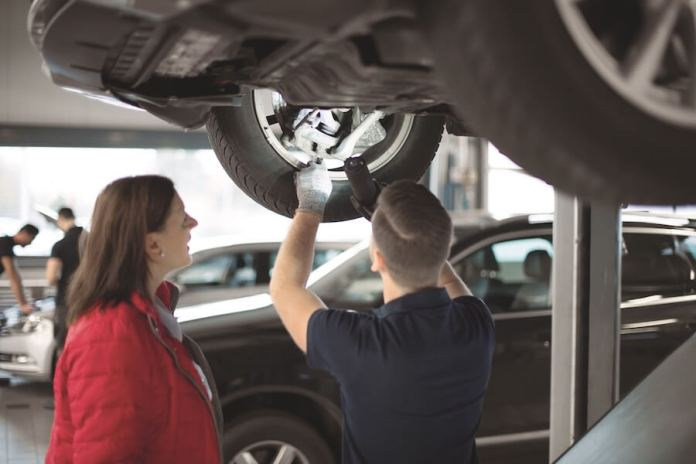 A female motorist on the left, speaks with an automotive repair technician on the right, while under a vehicle in the shop. They are discussing the vehicle's wheel.