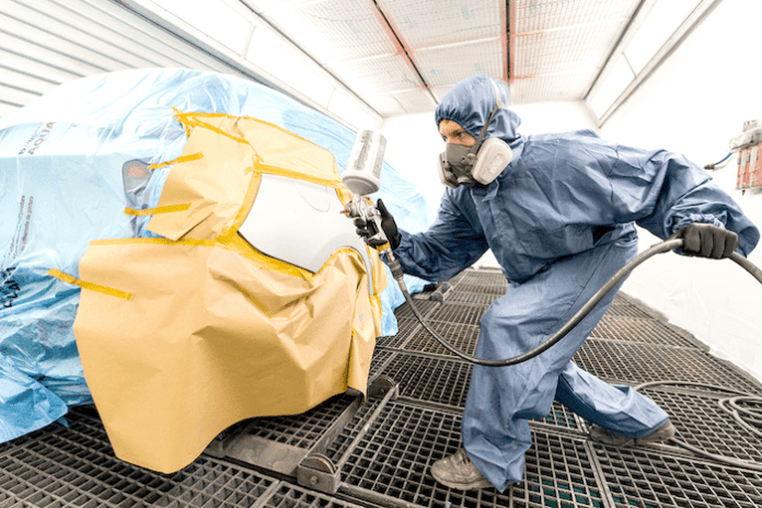 This image shows a body shop professional inside a spray booth, applying paint to a car body.