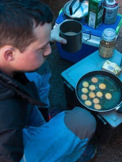 Angus prepares breakfast on a wet morning beneath Stanage Edge