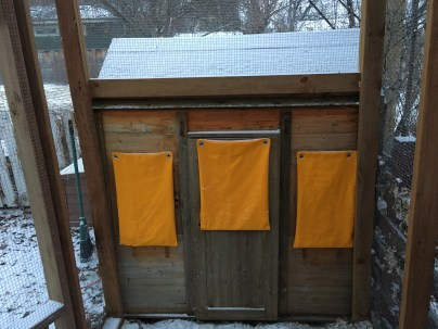 Three small window blankets installed on the coop.