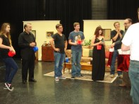 The cast and crew opens their Opening Night gifts. Photo by Jeff Knoll.