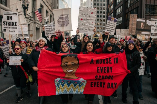 Striking Chicago teachers marching in the street, carrying a banner