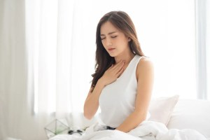 Woman in white pajamas suffering from Acid reflux while wake up on her bed in the morning