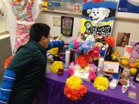 A student points out his family's contribution to the altar.