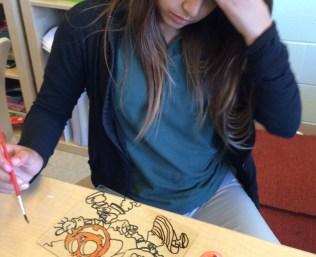 Students paint Día de los Muertos images...